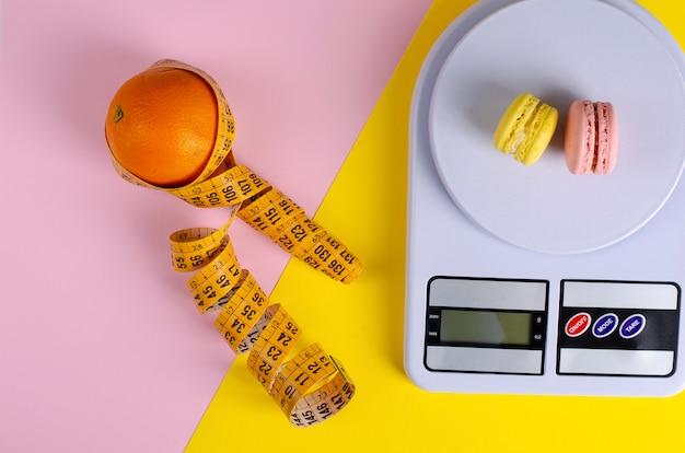 Une orange avec un ruban à mesurer, des balances de cuisine numériques avec des macarons sur rose et jaune