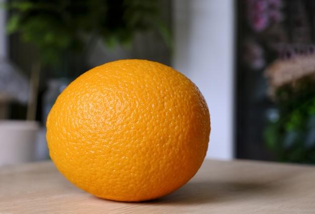 Orange savoureuse fraîche et brillante sur une table en bois, nourriture végétalienne naturelle. épluchure d'orange