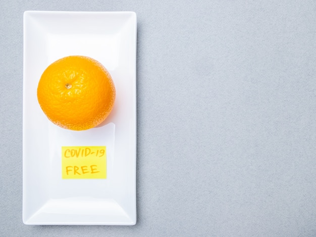 Une orange se trouve sur un masque médical bleu à l'intérieur d'une plaque en céramique rectangulaire blanche