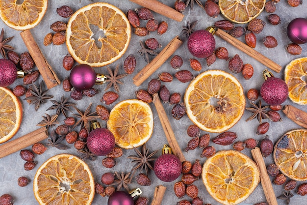 Orange séchée avec des boules de noël et des cynorrhodons sur la surface de la pierre.