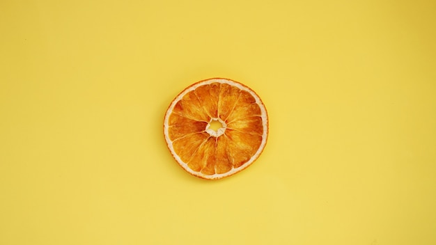 Orange séchée sur fond jaune. macro de tranche d'orange séchée