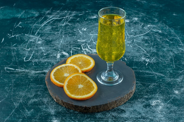 Orange en tranches à côté du jus de poire sur le plateau , sur fond bleu.