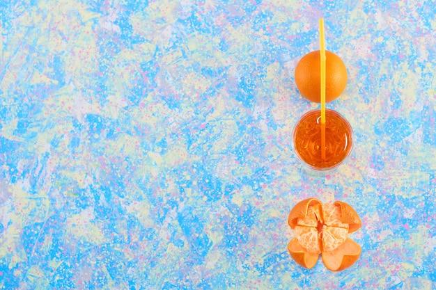 Orange et un verre de jus avec pipe jaune