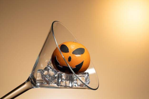Une orange avec un visage de citrouille dans un verre de martini avec de la glace.