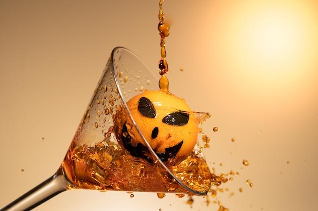 Une orange avec un visage de citrouille en verre de martini avec de la glace et des éclaboussures.