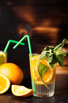 Orangeade biologique fraîche faite de fruits naturels sur fond de bois vintage