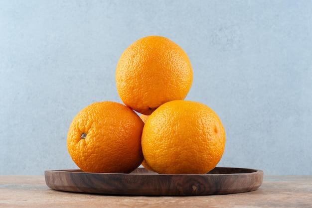 Oranges aigres fraîches sur plaque en bois