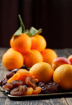 Oranges sur branche avec dattes, abricots secs et mûrs en vue de côté du plateau sur la table en bois