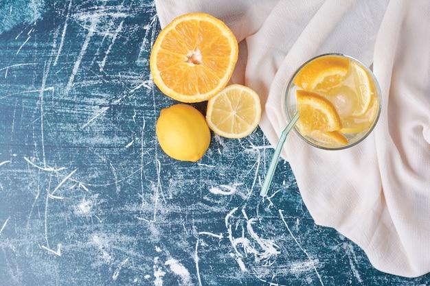 Oranges citronnées avec une tasse de boisson sur bleu.