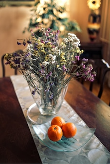 Oranges à côté d'un vase avec des fleurs