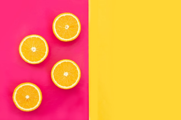 Oranges coupées en deux fruits sur fond rose avec fond jaune pour les textes