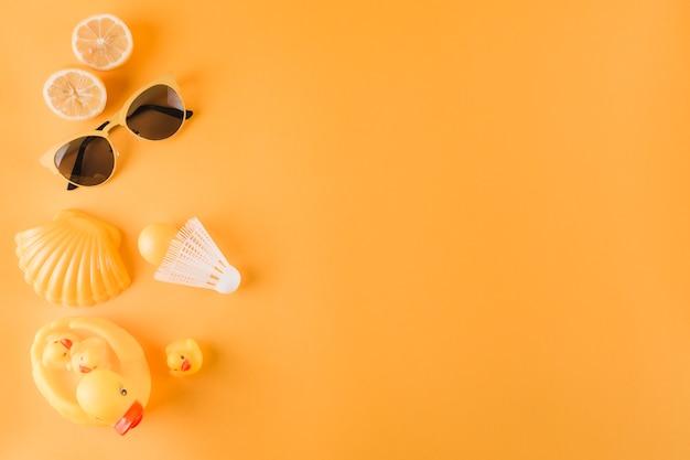 Des oranges coupées en deux; des lunettes de soleil; balle en plastique; volant; coquille saint-jacques et canard en caoutchouc sur fond coloré