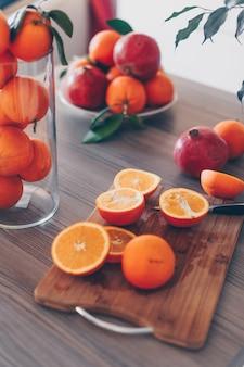 Oranges coupées en deux sur une planche à découper et une table avec des fleurs
