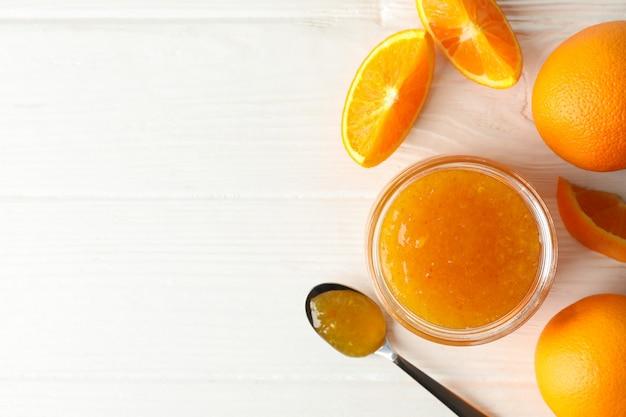 Oranges, cuillère et bocal en verre avec de la confiture sur bois blanc
