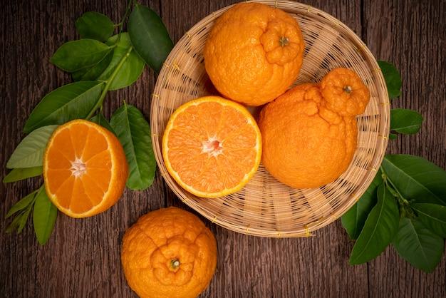 Oranges dekopon avec des feuilles en surface en bois