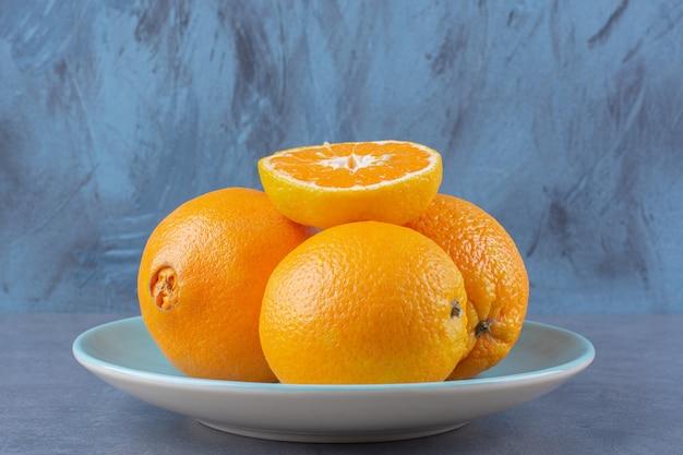 Oranges empilées les unes sur les autres sur une table en marbre plateon.