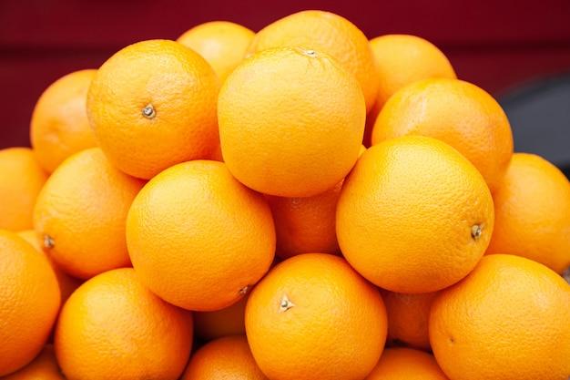 Oranges sur l'étal de marché. texture fond orange mûres fruits juteux.