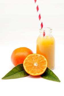 Oranges avec feuilles et jus d'orange sur blanc