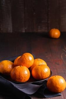 Oranges fraîches sur bol brun foncé