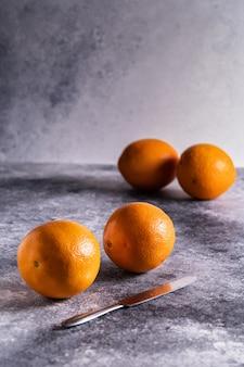 Oranges fraîches et couteau sur table en béton