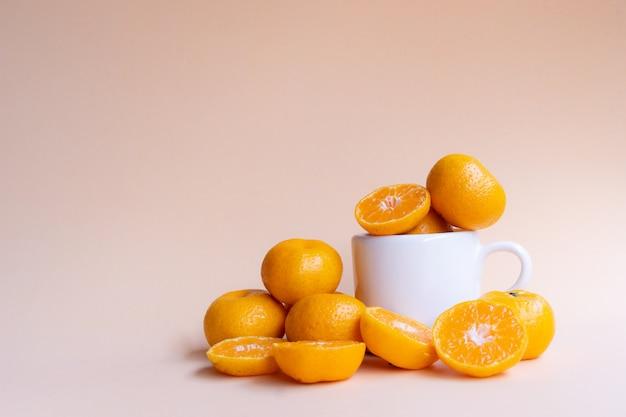 Oranges fraîches entières et à moitié coupées avec une tasse en céramique blanche sur un fond crème doux