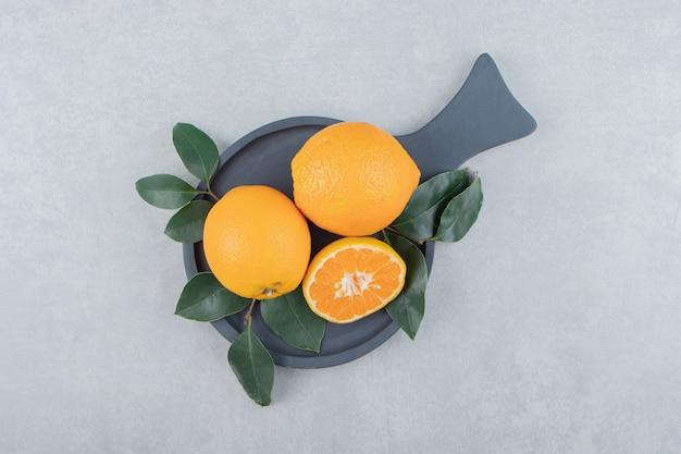 Oranges fraîches avec des feuilles sur une planche à découper noire.