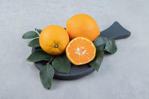 Oranges fraîches avec des feuilles sur une planche à découper noire
