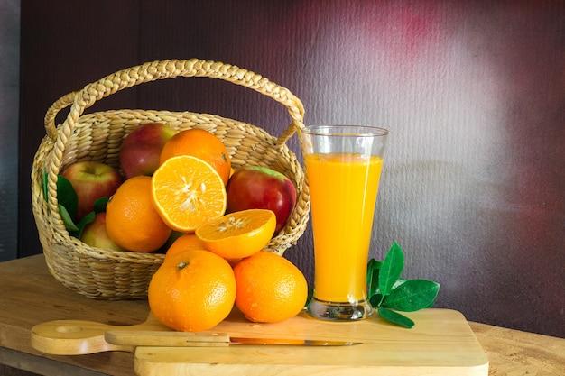 Oranges fraîches et jus de raisin violet sur la table./botte d'oranges avec des gouttelettes d'eau