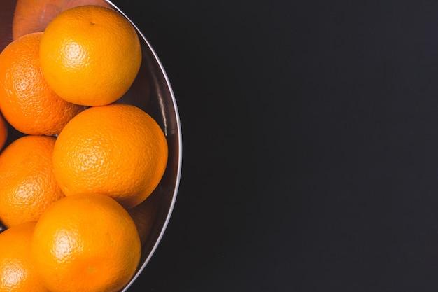 Oranges fraîches juteuses dans un bol en acier sur fond noir. agrumes. fruits à la vitamine c