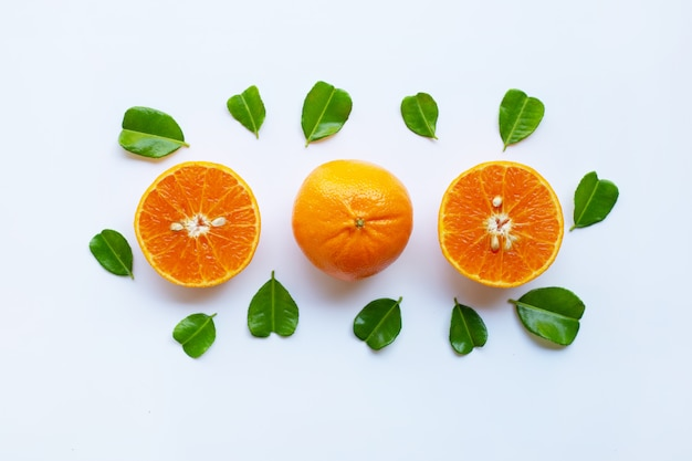 Oranges fraîches avec la moitié des feuilles de citron vert kaffir bergamote, en forme de cœur sur fond blanc