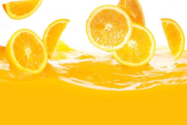 Oranges fraîches tombant dans le jus