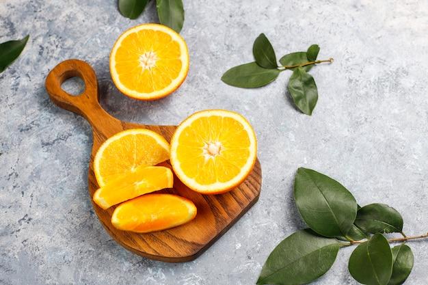 Oranges fraîches en tranches sur une planche à découper sur une surface en béton