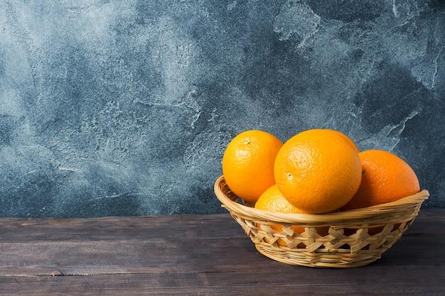 Oranges de fruits frais dans un panier sur un fond sombre.