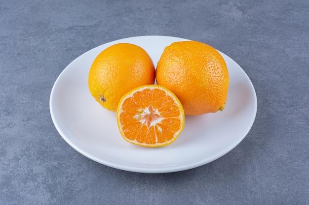 Oranges juteuses sur plaque sur table en marbre.