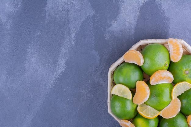 Oranges mandarines vertes dans un panier en bambou