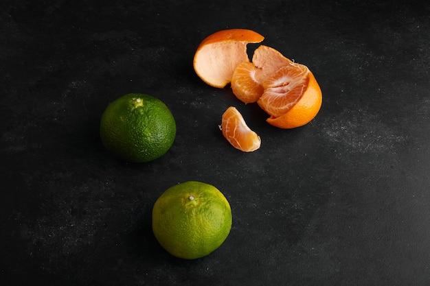 Oranges mandarines vertes et jaunes sur fond noir, vue de dessus.