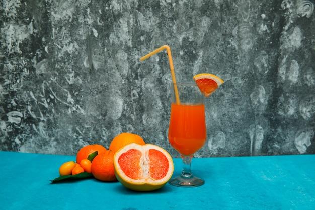 Oranges mandarines avec vue latérale orange et jus sur table texturée bleue et texture grise