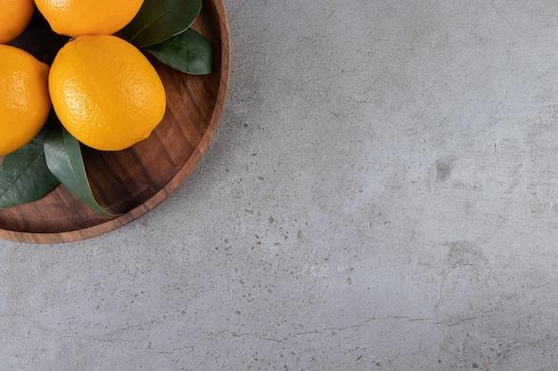 Oranges mûres sur une assiette en bois, sur la table en marbre.