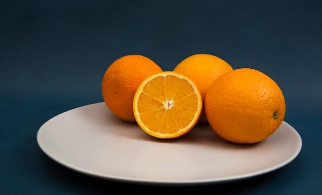 Oranges mûres sur une assiette sur une table sombre