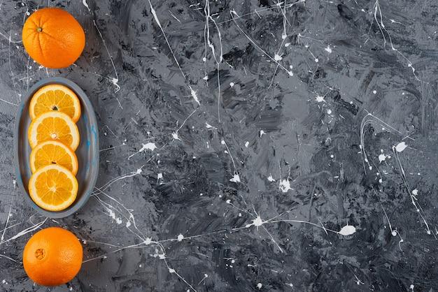 Oranges mûres entières et tranchées placées sur une assiette bleue.