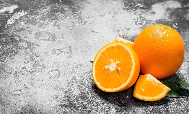 Oranges mûres avec des feuilles vertes sur fond rustique