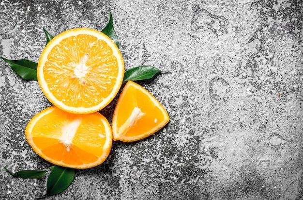 Oranges mûres avec des feuilles vertes. sur fond rustique.