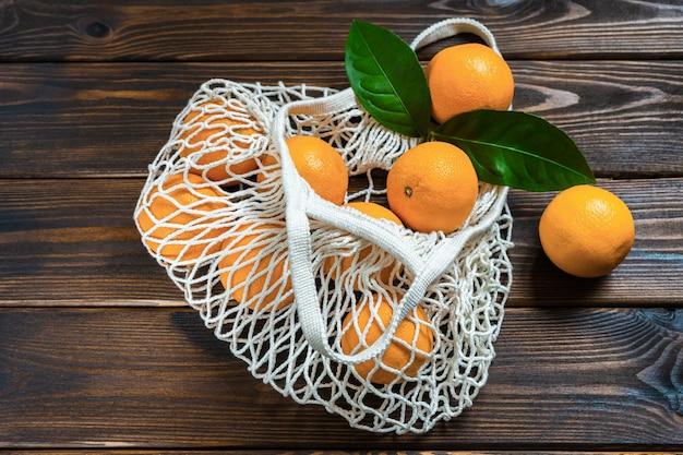 Oranges en oranges dans un sac en filet écologique sur une table en bois