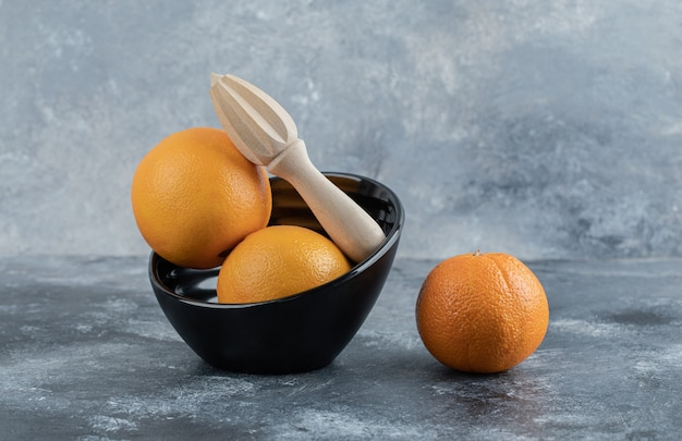 Oranges et outil de compression sur table en marbre.