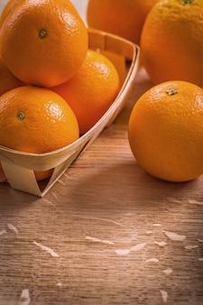 Oranges en panier en osier sur planche de bois