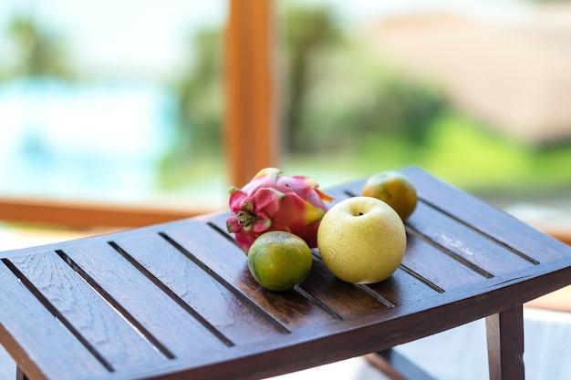 Une oranges, poire et fruit du dragon sur une petite table en bois
