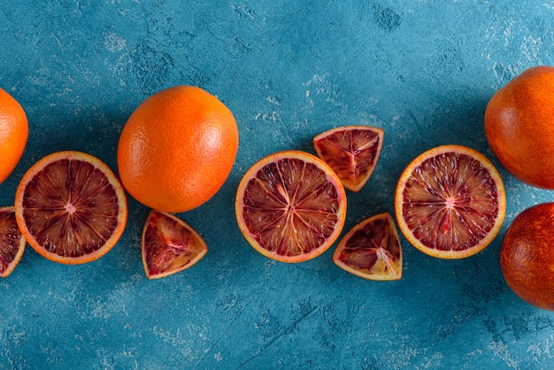 Oranges rouges, tranches, moitiés sur fond bleu, composition alimentaire, vue de dessus, mise à plat, espace copie
