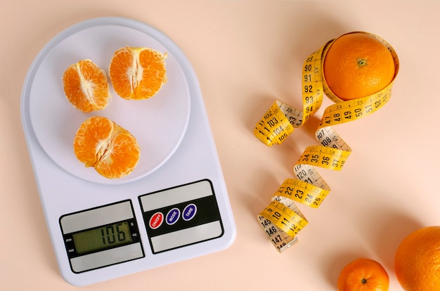 Oranges avec ruban à mesurer et balance de cuisine numérique.