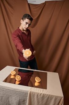 Oranges sur la salle des miroirs et tissu homme émotionnel.