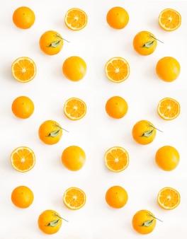 Oranges tranchées et entières sur une surface claire